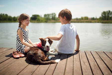 cute boy and girl sitting by the river, smiling, cuddling the dog