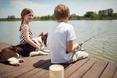 boy sitting on dock by the river, fishing with his dog and little smiling girl