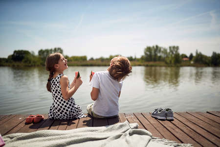 cute minor caucasian brother and sister laughing at riverside,  sitting by the river eating watermelon