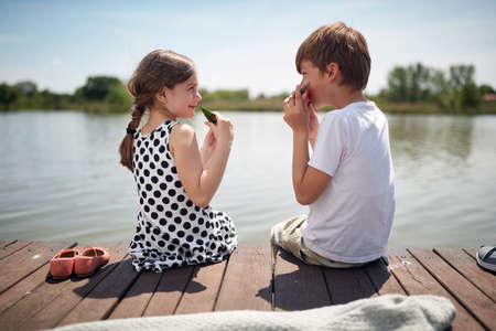cute minor caucasian couple sitting by the river eating watermelon