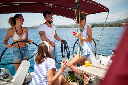 Friends have a woderful time on a yacht on beautiful weather