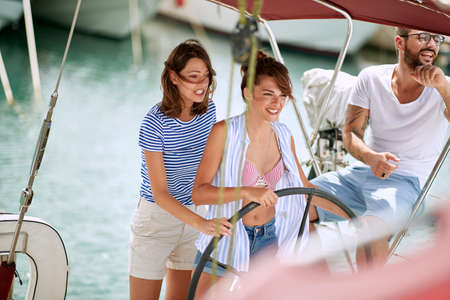 Friends enjoy steering a yacht on sunny day