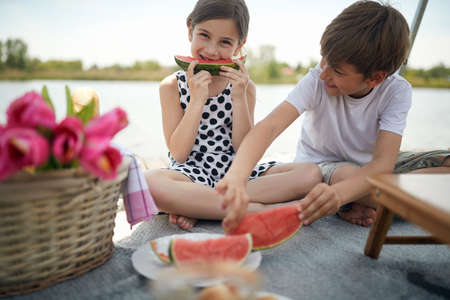 cute girl and boy eating watermelon at picnic by the river. cuteness overload Foto de archivo