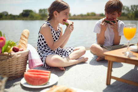 minor caucasian boy and girl eating watermelon at picnic by the river
