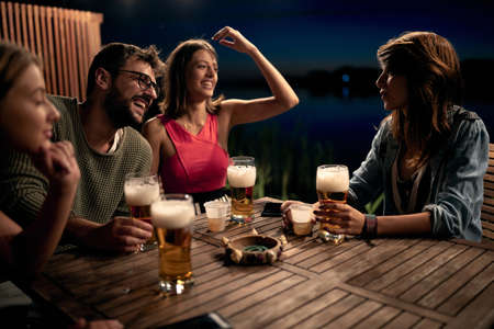 Smiling friends talking and drinking beer and enjoying a beautiful evening. Archivio Fotografico