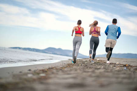 Enjoying By The Sea. young People active runner running on beach at morning. Archivio Fotografico