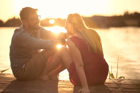 Smiling man and woman in love. Romantic sunset at lake.