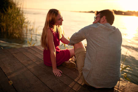 Smiling couple at river enjoying together on romantic sunset.