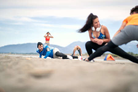 Young man doing fitness workout at a beach, enjoying at vacation and exercise.