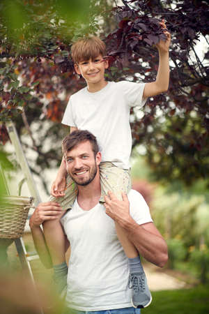 A boy on the shoulders of his father posing in the garden on a beautiful day