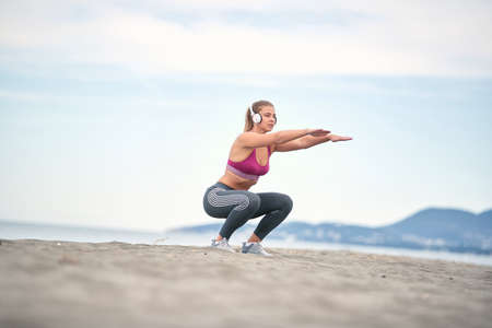 Girl listening to music and doing exercises on the beach.Young woman squatting legs.