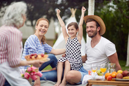 Happy family excited about cake on picnic in the backyard