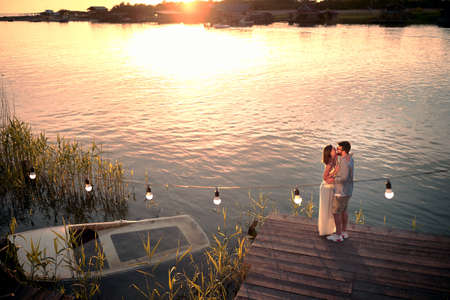 Smiling couple at river enjoying together on romantic sunset and kissing.