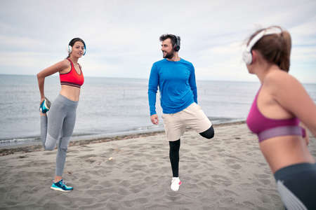 Young attractive people having fun on beach and doing some fitness workout.