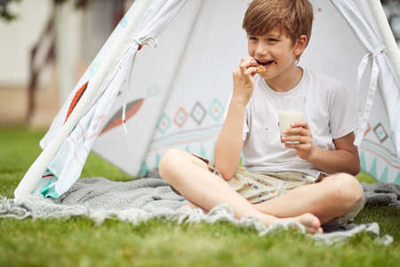 Young boy enjoying the food in a camp on a sunny day