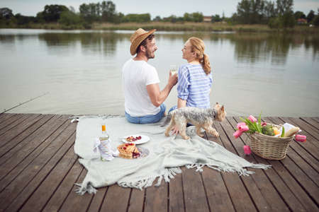 Happy spouse enjoying a picnic on the dock of the lake