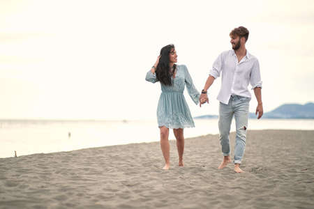 Happy couple holding hands in romanitic walk by the sea. Standard-Bild