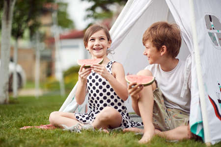 Young boy and girl excited about watermelon in a small camp Standard-Bild