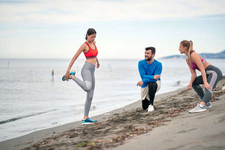 Prepare for Jogging. Group of Young People Exercising On The Beach. Standard-Bild