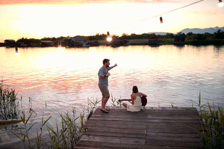 Romantic  couple plays guitar, singing and have fun on the river at beautiful sunset.