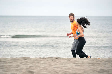 Fitness young couple  running along beach.Enjoying at vacation and exercise at the beach.