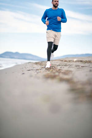 To Be Young exercise. Healthy active men runner running on beach.