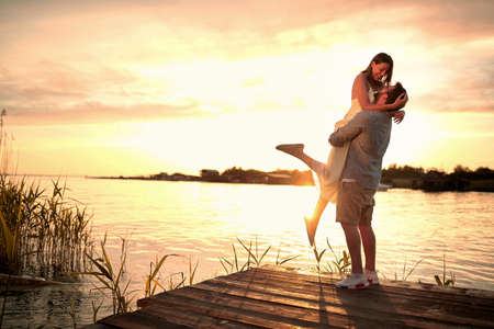 Enjoying By The River.Romantic smiling couple in love dating at sunset at river. Standard-Bild