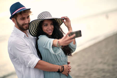 Young romantic  couple in an embrace  on sea beach make selfie.