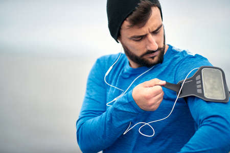 Man runner listening to music jogging with armband for smart phone. Fit young man fitness model working outdoor at beach.