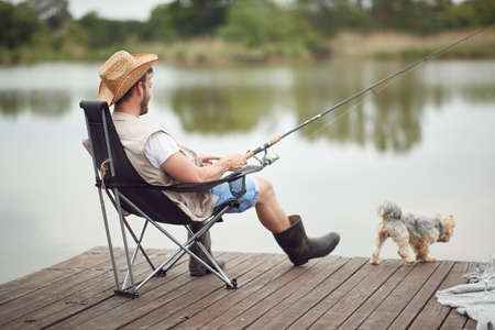 A man enjoying fishing on a dock with his dog