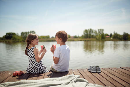 Happy Brother and sister sitting on the dock and eating a watermelon on a beautiful weather