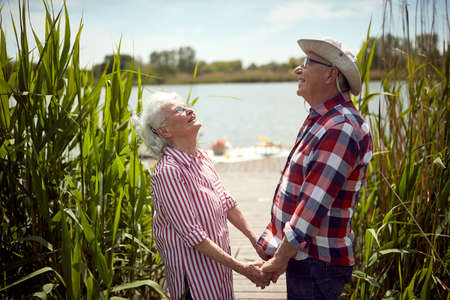 Happy old couple on picnic enjoying the sun