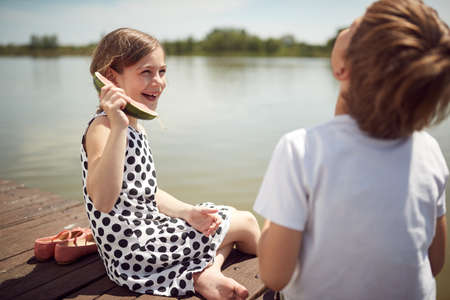 Brother and sister making jokes on the dock of the lake Standard-Bild