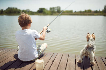 Young boy fishing on a lake with his dog on a sunny day
