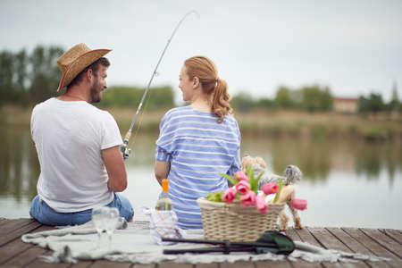 Happy spouses enjoy fishing and a picnic with their dog on a beautiful weather Standard-Bild