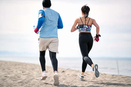 Fitness young man and woman  running along beach together.