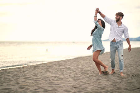 Romantic happy  couple is dancing by the sea at beach. Standard-Bild