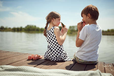 Brother and sister sitting on the dock and eating a watermelon on a sunny day Standard-Bild