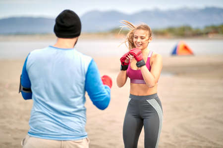 Boxing sparring boxers at beach exercise. Man and young woman  sparring  together.