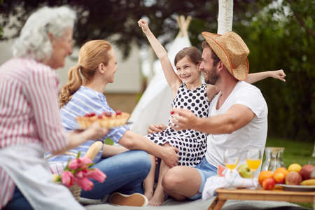 Happy family excited about cake on picnic in the backyard on a beautiful day Standard-Bild