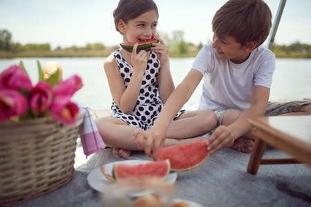 Happy brother and sister enjoy watermelon on a picnic on the lake Standard-Bild
