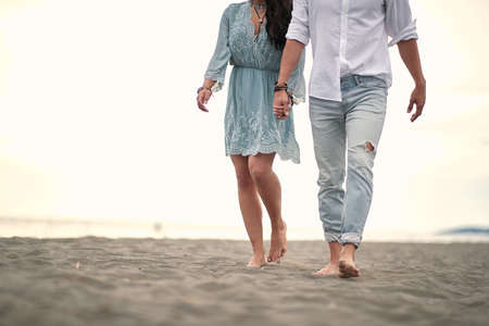Romantic beautiful walk by the sea. Couple holding hands.