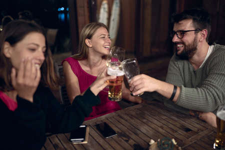 Smiling man and woman enjoying at evening fun and drinks beer together . Friends enjoying drinks together.