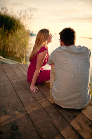 Smiling man and woman at river enjoying together on romantic sunset. Standard-Bild