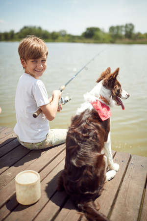 Young boy enjoys fishing with his dog on a sunny day
