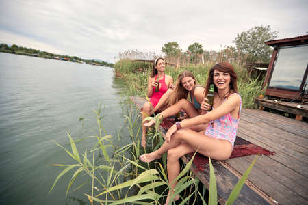 Summer party on lake.Young female friends relaxing on the river.