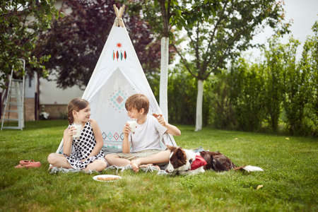 Kids have a meal in camp in a backyard on a sunny day