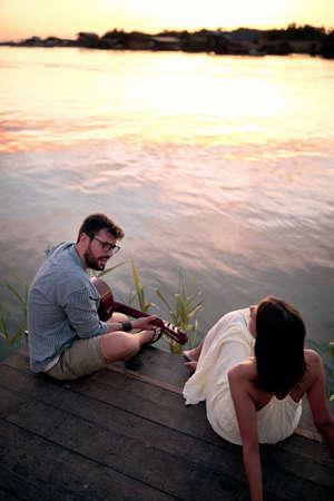 Romantic couple  plays guitar on the river at beautiful sunset.