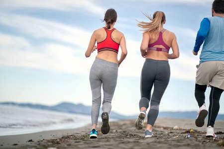 Enjoying By The Sea.People active runner running on beach at morning. Standard-Bild