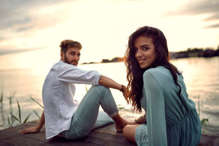 Young man and woman in love having romantic tender moments on the river.